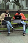 Minsk, Belarus: two students working on their laptop computers on a street bench - photo by A.Dnieprowsky