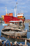 Moroni, Grande Comore / Ngazidja, Comoros islands: the freighter 'Moroni' and old dhow hulls - Port aux Boutres - photo by M.Torres