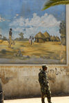 Eritrea - Asmara: soldier in front of a mural with a village scene - photo by E.Petitalot