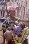 Côte d'Ivoire - Smiling lady and her baby - breast feeding outdoors (photo by J.Filshie)