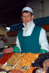 Kazakhstan, Almaty:green market, or Zelyoni Bazaar - Uzbek merchant with gold teeth selling dried fruits - photo by M.Torres