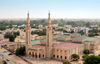 Nouakchott, Mauritania: the Saudi Mosque aka Grand Mosque, seen from above, with the city's skyline in the background - King Faisal avenue and Mamadou Konate street - la Mosquée Saoudienne - photo by M.Torres