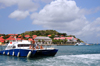Gustavia, St. Barts / Saint-Barthélemy: a divers' boat returns to the harbour - museum and local government buildings in the background - tip of Gustavia Peninsula - photo by M.Torres