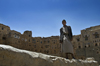 Hababah, Sana'a governorate, Yemen: young man standing on wall in front of Old Town buildings - photo by J.Pemberton
